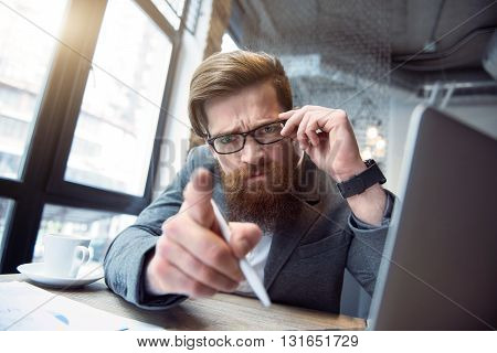 Hey you. Bearded emotional brutal man sitting at the table and touching his glasses while pointing you