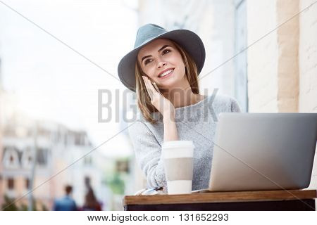 Be in good spirits. Cheerful and smiling young woman speaking by mobile phone with her boyfriend and using a laptop while sitting in a cafe and drinking nice coffee