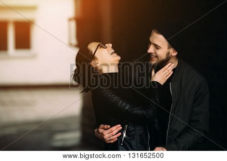 young beautiful couple posing in the side street at the camera