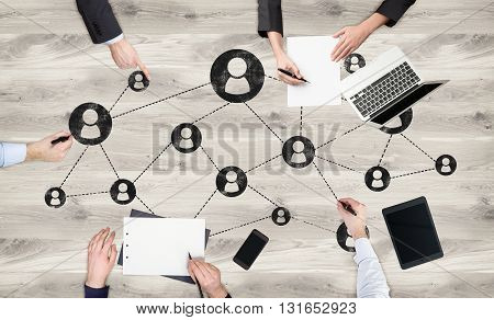 Social networking concept with businesspeople team working on wooden desktop with network system and electronic devices