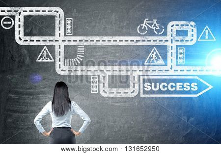 Businesswoman looking at road to success sketch on chalkboard background