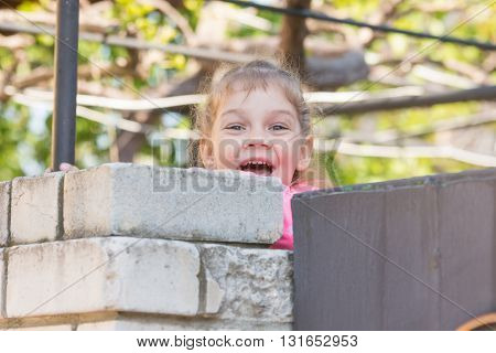 Five-year Girl Smiling Looked Out From Behind The Wall