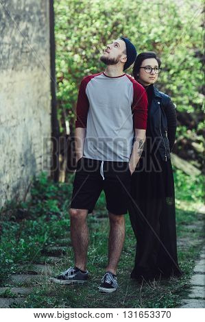 young beautiful couple posing next to an abandoned house