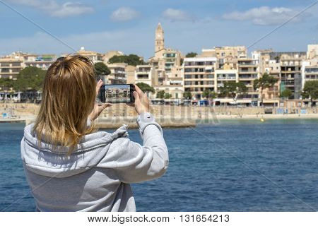 Young blonde woman sightseeing and taking photos with her smartphone in Porto Cristo Spain.