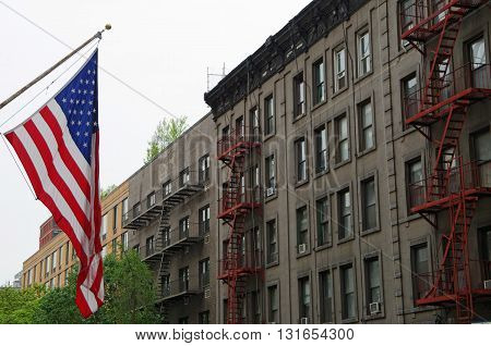 American flag on NYC street with background building fire escapes