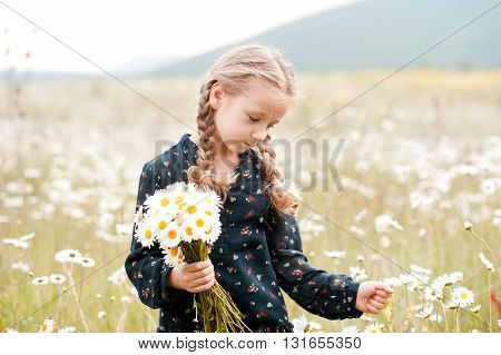 Cute baby girl holding chamomile in meadow. Childhood. Summer time.