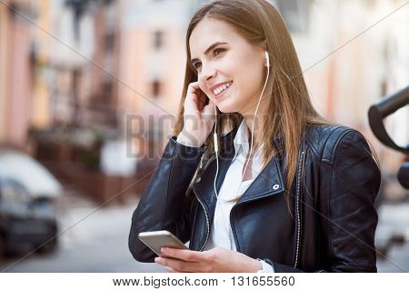 Musical rhythm.  Positive and smiling young woman listening to music using her mobile phone and earphones while being in a big city