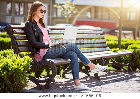Beautiful day.  Positive and cheerful young woman using a laptop while sitting on a bench and  being in a park