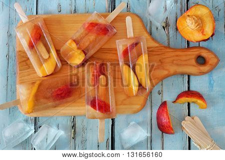 Homemade Peach Iced Tea Popsicles, On Paddle Board Against Rustic Blue Wood Background