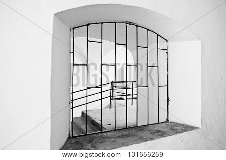 Arched Window With Metal Grating. Black And White