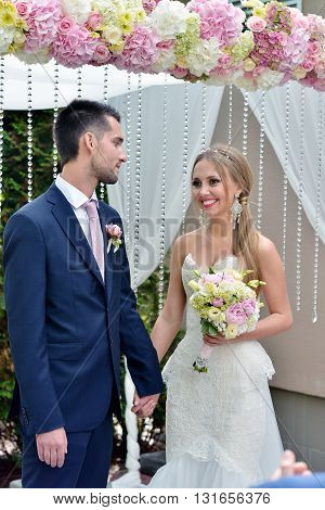 Beauty bride and handsome groom are registering the marriage. Wedding couple is marrying. Beautiful model girl in white dress and in lace veil. Man in suit. Female and male portrait. Cute lady and guy