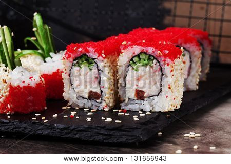 beautiful sushi roll with crab cucumber and tobiko caviar in a restaurant on a black graphite board sesame
