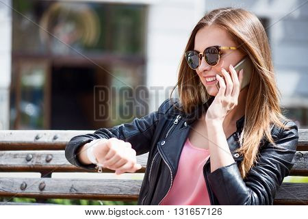Arranging a meeting. Content and merry young woman looking at a smart watch while sitting on a bench in a park and making a phone call
