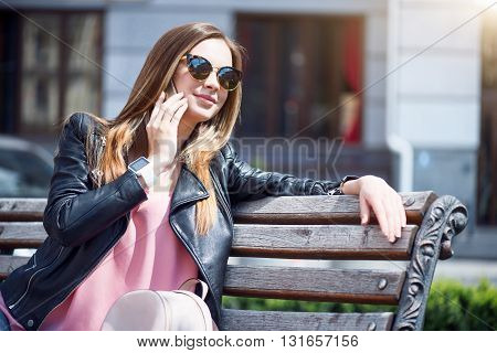 Modern devices in our life. Cheerful and confident young woman speaking per cell phone while sitting on a bench in a park