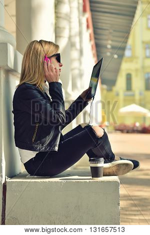 girl sitting with tablet and listening to music side view