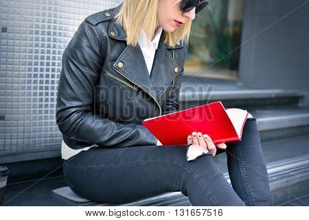young hipster girl reading a red book