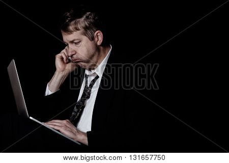 Side view of stressed business man on cell phone while looking at computer screen. Dark background with light on subject.