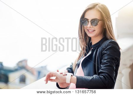What time. Cheerful and content young woman looking at her smart watch and waiting for somebody