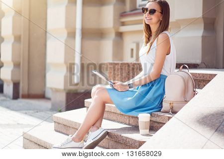 Enjoy my free time. Smiling and positive young woman using a digital tablet while sitting on the stairs and drinking nice coffee