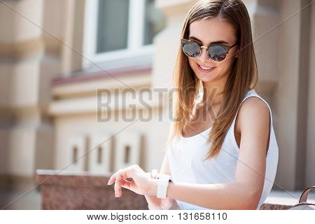 Time goes quickly. Smiling and positive modern young woman looking at her smart watch while thinking about time and being in a very good mood
