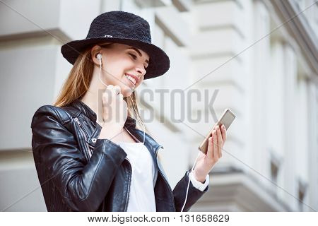 My favorite hits.  Smiling and merry modern young woman using her cell phone while listening to music and being in a very good mood