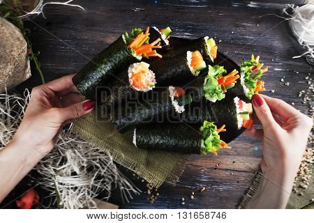 roll sushi black background hands tray dish different tastes crab carrots lettuce tofu salmon still life home stylish wooden worktops table