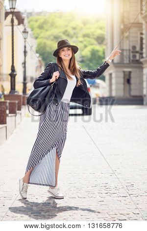 Hailing a cab.  Positive and very cheerful modern young woman hailing a taxi being in a big city