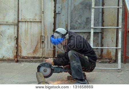 KIEV REGION, UKRAINE - MAR 31, 2016: Worker on the reconstruction old garage in countryside .March 31, 2016 Kiev Region, Ukraine