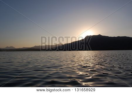 Sunrise over mountain peak seen from a fisherman's boat