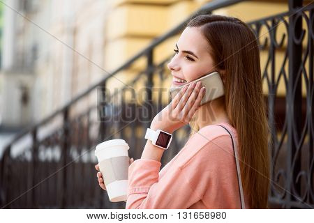 Important call.  Smiling and happy modern young woman speaking per cell phone and drinking coffee while being outside