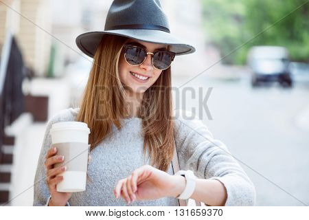 Hurry up. Cheerful and glad modern young woman drinking nice coffee while being outside and looking at her smart watch