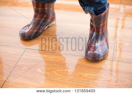 kid wearing waterproof gumboots and standing on wet floor