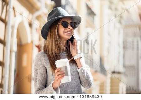 Keeping in touch.  Smiling and merry modern young woman drinking nice coffee while being outside and specking per cell phone