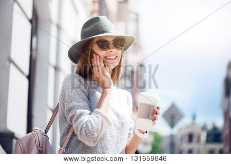 Sunny day.  Positive and cheerful modern young woman speaking per cell phone and drinking nice coffee while being outside