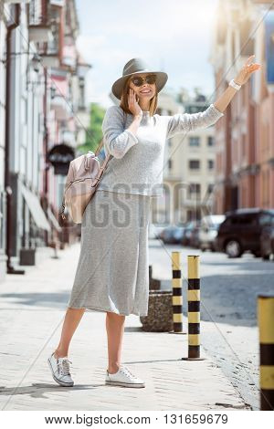 Travelling.  Smiling and positive modern young woman speaking per cell phone and hailing a taxi