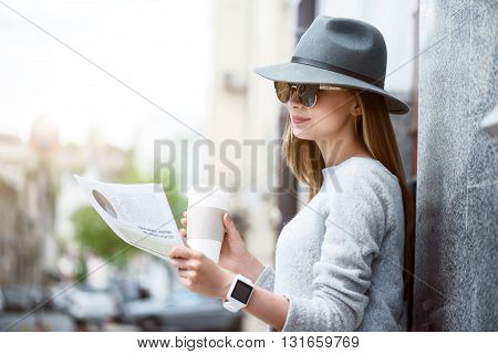 Involved in reading.  Cheerful and pleasant modern young woman reading some articles in a newspaper and drinking nice coffee while being outside