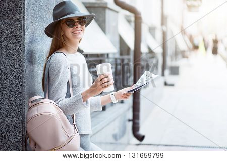 My leisure.  Smiling and positive  modern young woman reading some articles in a newspaper and drinking nice coffee while being outside