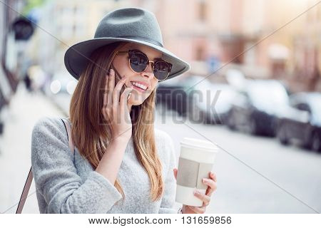 Sharing moment.  Smiling and merry modern young woman talking per cell phone while drinking nice coffee and being outside