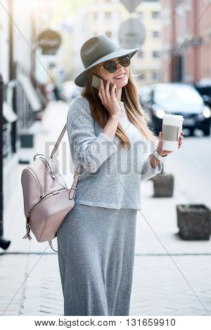 24 hours per day.  Smiling and cheerful modern young woman speaking per cell phone while drinking nice coffee and being outside