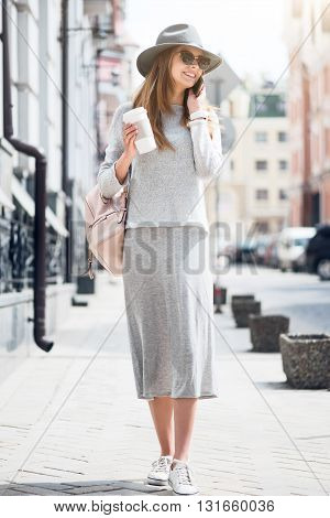 Cell phone usage.  Positive and happy modern young woman speaking per mobile  phone while drinking nice coffee and being outside