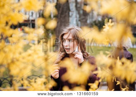 Portrait of attractive young woman standing and talking on cell phone in park