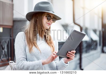 Digital tablet usage.  Cheerful and positive modern young woman using a digital tablet while and being outside