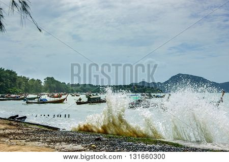 High tide waves flood over beach wall at Rawai beach Phuket southern Thailand