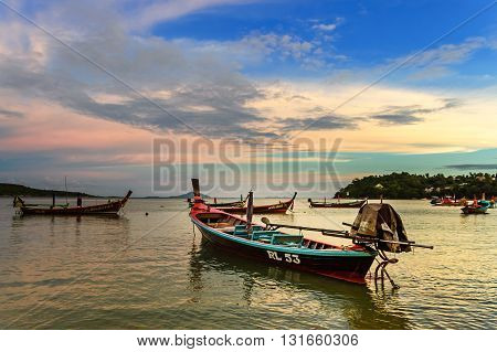 Rawai Thailand - August 17 2014: Traditional long-tail boats used for tourist trips & fishing moored in bay at sunset off Rawai beach on southern tip of Phuket southern Thailand