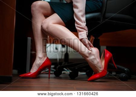 Business woman touching feet with her hand.