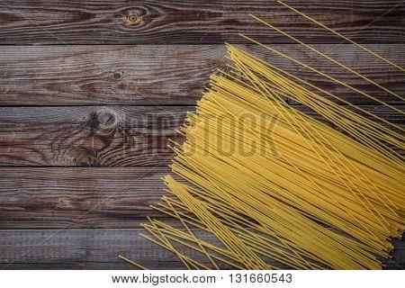 Yellow long spaghetti on black background. Raw spaghetti.