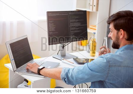 Today is a good day. Delighted young man having a drink while programming on his computer