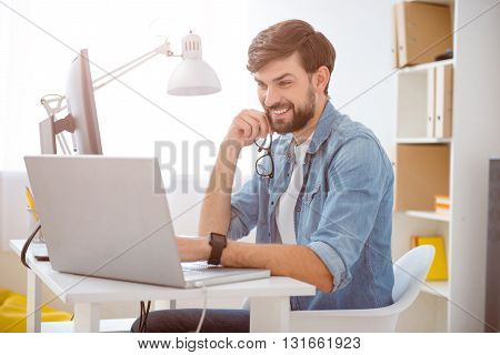 In a good mood. Young bearded guy smiling while using his laptop and holding glasses in his hand