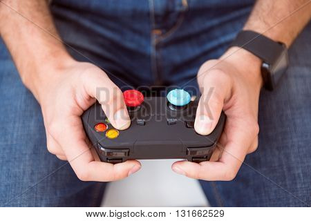 Ready to win. Close up of two hands of a man holding a videogame controller