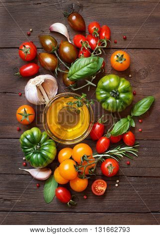 Colorful tomatoes garlic olive oil and herbs on a wooden table